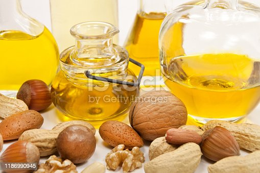 Various nuts and oil on white background