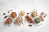 Various Nuts in  bowls on white background, top view, copy space. Nuts assortment - pecans, hazelnuts, walnuts, pistachios, almonds, pine nuts, peanuts, pumpkin seeds.
