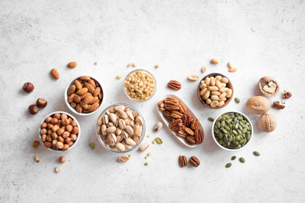Various Nuts in  bowls Various Nuts in  bowls on white background, top view, copy space. Nuts assortment - pecans, hazelnuts, walnuts, pistachios, almonds, pine nuts, peanuts, pumpkin seeds. nut food stock pictures, royalty-free photos & images
