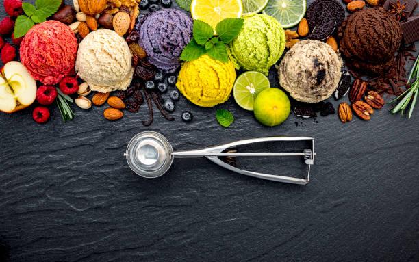 Verschiedene eis geschmack Kugel Heidelbeere, Limette, Pistazien, Mandel, Orange, Schokolade und Vanille auf dunklen Stein Hintergrund eingerichtet. Sommer- und Süßes Menükonzept. – Foto