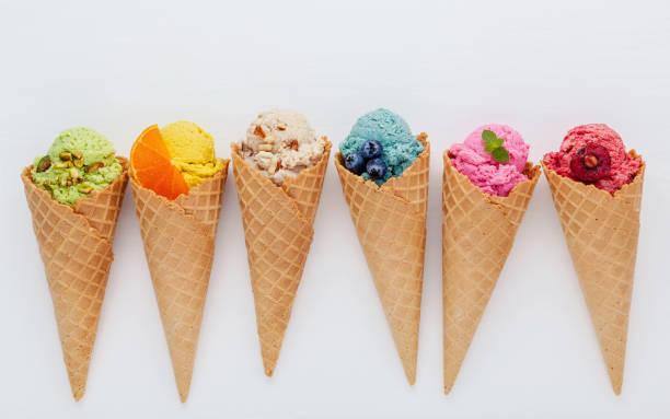 Verschiedene Eissorten Geschmack im Kegel Heidelbeere, Erdbeere, Pistazie, Mandel, orange und Kirsche Setup auf weißem Hintergrund aus Holz. Sommer und süße Menü Konzept. – Foto