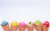 アイスクリームの様々 な味のコーン ブルーベリー、ストロベリー、ピスタチオ、白い木製の背景にアーモンド、オレンジ、チェリーのセットアップ。夏、甘いメニュー コンセプト。