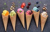 アイスクリームの様々 な味のコーン ブルーベリー、ストロベリー、ピスタチオ、暗い石の背景にアーモンド、オレンジ、チェリーのセットアップ。夏、甘いメニュー コンセプト。