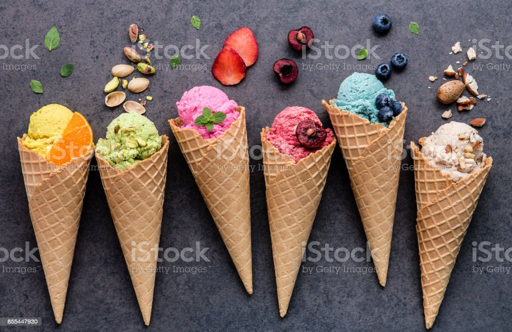 Various of ice cream flavor in cones blueberry ,strawberry ,pistachio ,almond ,orange and cherry setup on dark stone background . Summer and Sweet menu concept. stock photo