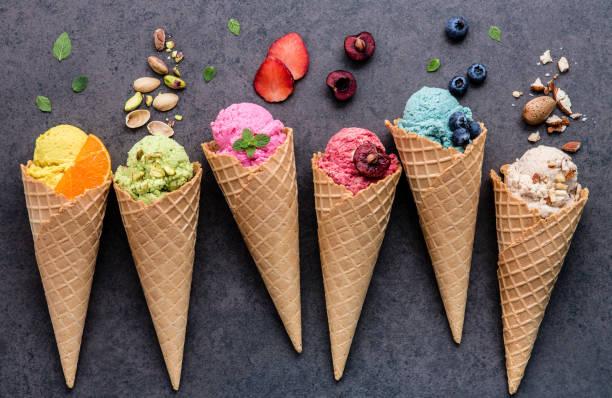 Verschiedene Eissorten Geschmack im Kegel Heidelbeere, Erdbeere, Pistazie, Mandel, orange und Kirsche Setup auf dunklem Stein. Sommer und süße Menü Konzept. – Foto