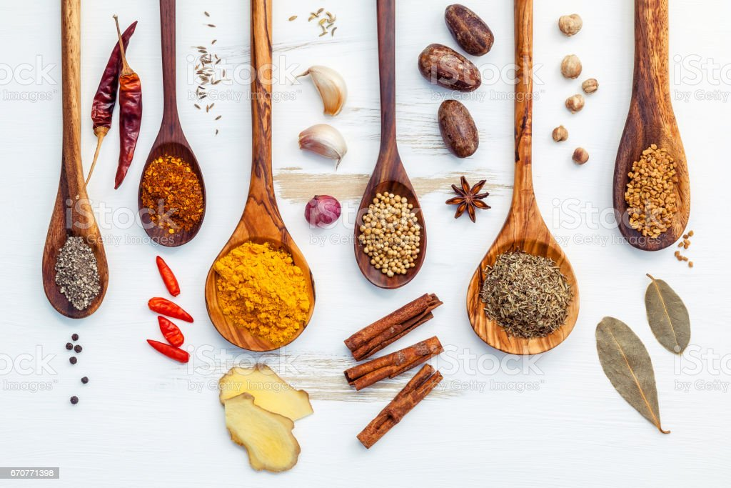 Various of Indian spices and herbs in wooden spoons. Flat lay of spices ingredients chili ,paprika ,peppercorn, dried thyme, cinnamon,star anise and curry powder on the shabby wooden. stock photo