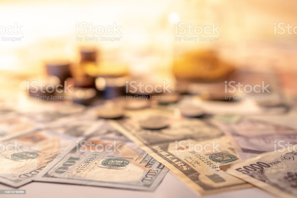 Various of international money coin and banknote with blurred hourglass in the background. Time investment with currency exchange concept. Focus on dollar banknote. stock photo