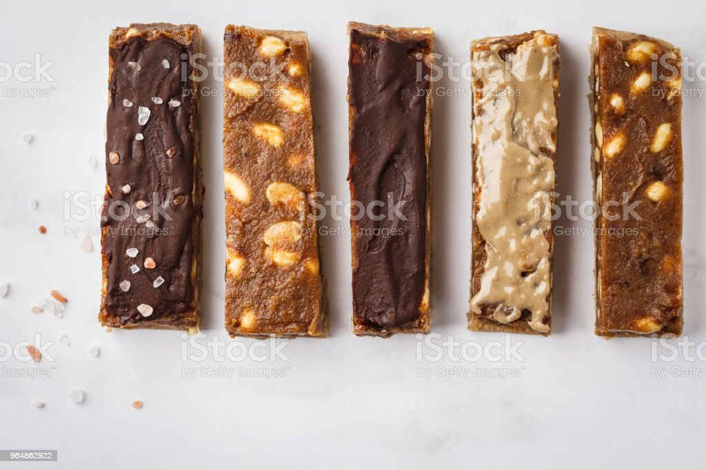 Various of raw vegan homemade chocolate peanut candy bars, top view.  Healthy lifestyle and raw vegan food concept. royalty-free stock photo