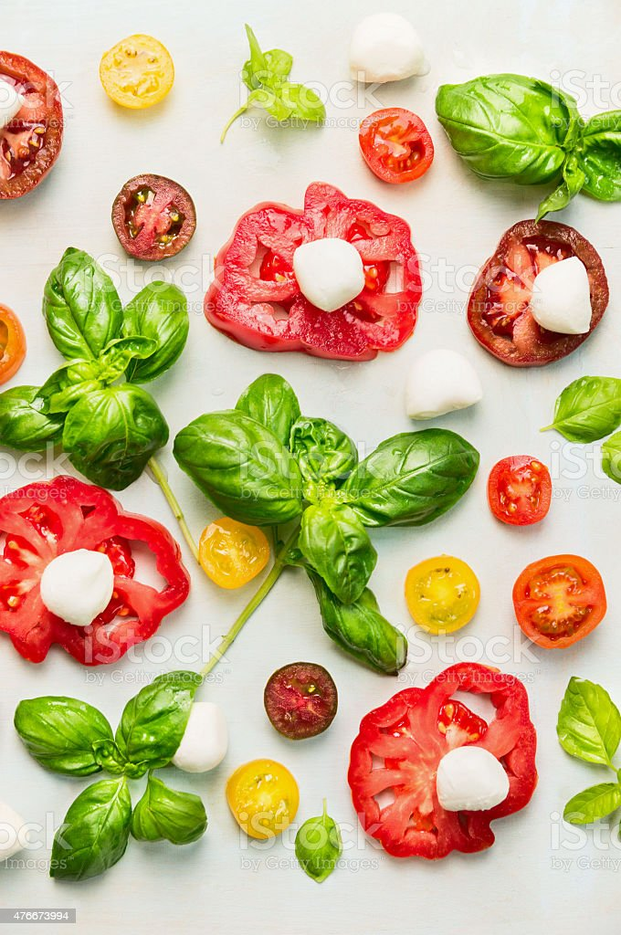 various of sliced tomatoes with mozzarella cheese and fresh basil stock photo