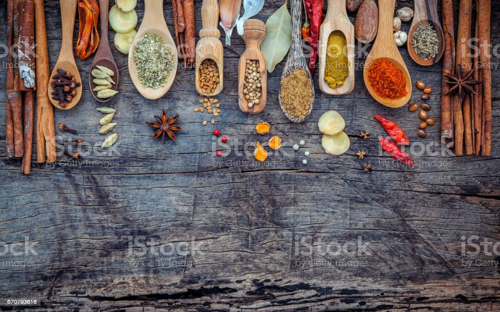 Various of spices and herbs in wooden spoons. Flat lay of spices ingredients chilli ,pepper corn, garlic, thyme, oregano, cinnamon, star anise, nutmeg, mace, ginger and bay leaves on shabby wooden. stock photo