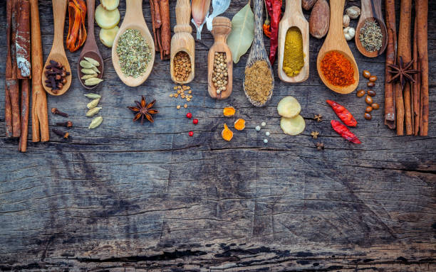 various of spices and herbs in wooden spoons. flat lay of spices ingredients chilli ,pepper corn, garlic, thyme, oregano, cinnamon, star anise, nutmeg, mace, ginger and bay leaves on shabby wooden. - chińskie ziołolecznictwo zdjęcia i obrazy z banku zdjęć