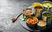 istock Various open tin cans of canned food on a stone Board with a fork. 1155944924