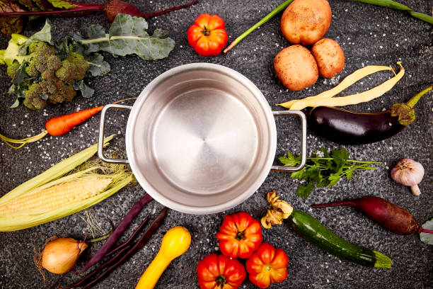 Verschiedene Bio-Gemüse-Zutaten rund um leere Kochtopf auf schwarzem Hintergrund. Ansicht von oben. Flach liegen. – Foto