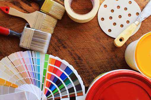 various painting tools, accessories and color samples for home renovation on wooden background .
