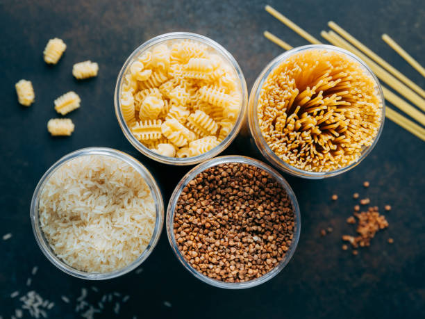 Various pasta and cereal grains in plastic jars for a long storage. stock photo