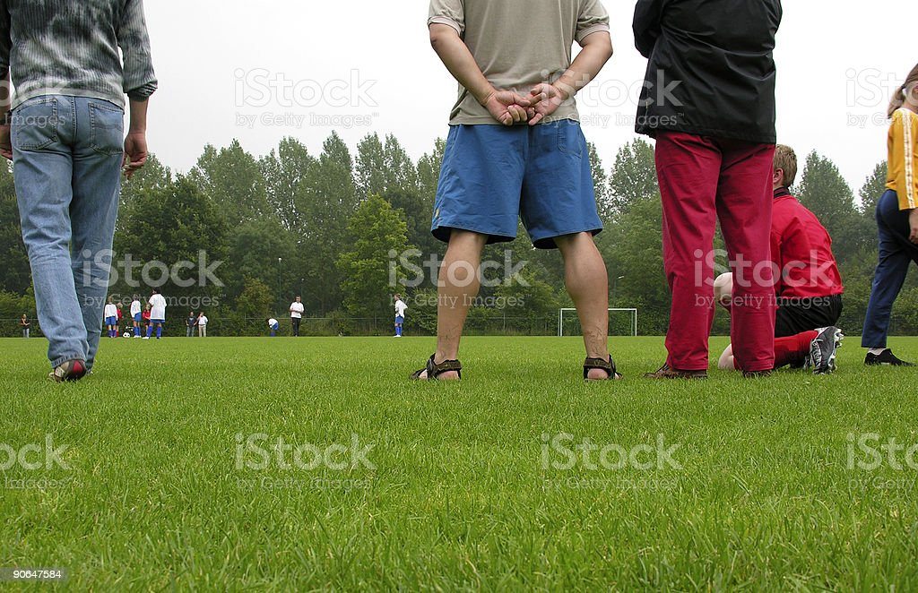 Various people watching a soccer game outdoors stock photo