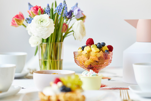 Various photos of a spring decorated table with waffles, fruit, fresh flowers and juice