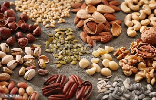 A variety of healthy and organic nuts and seeds in piles on a slate surface.