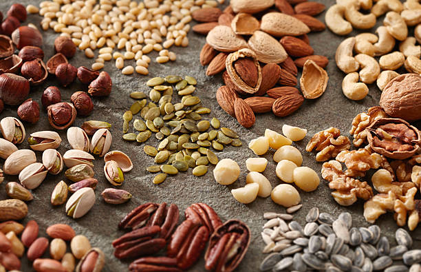 various piles of nuts and seeds - food allergies stock photos and pictures