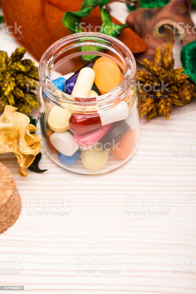 Various pills and capsules in glass container with green stock photo
