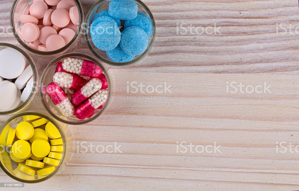 Various pills and capsules in glass containers top view stock photo