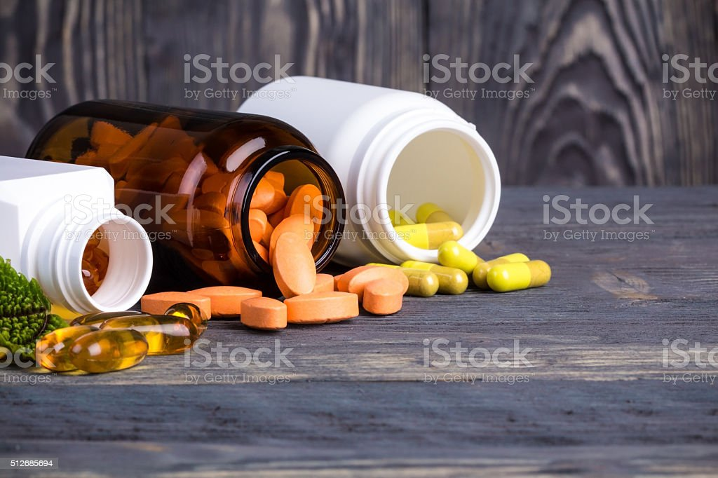Various pills and containers with green leaves stock photo