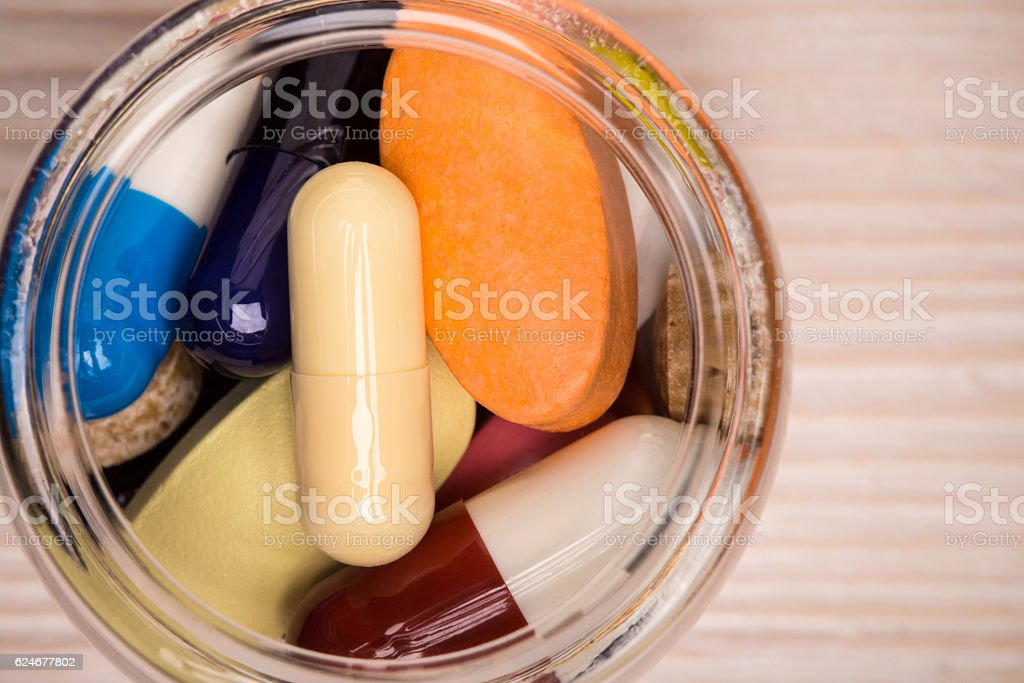 Various pills in transparent glass container top view stock photo