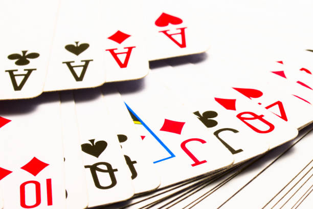 various playing cards closeup against a combination of four aces stock photo