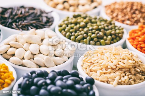 Various raw legumes and rice in white bowls
