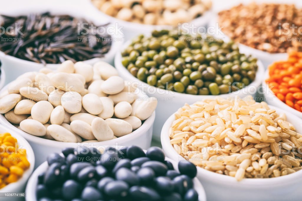 Various raw legumes and rice in bowls stock photo