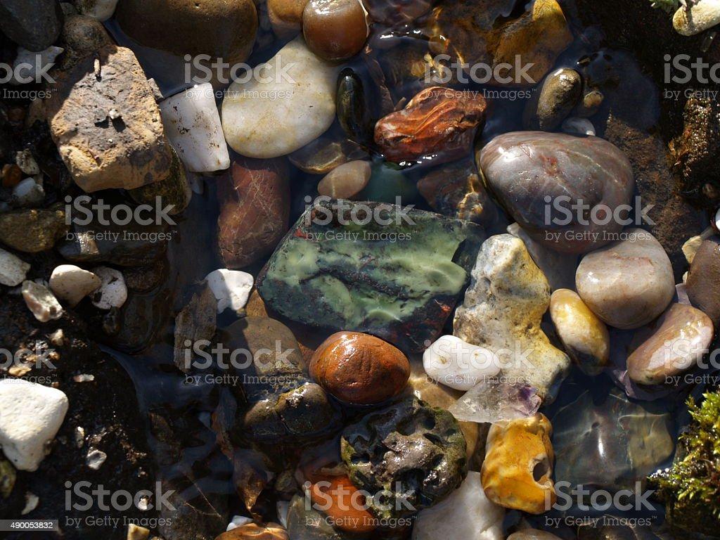 Various rocks in water, lapidary stock photo