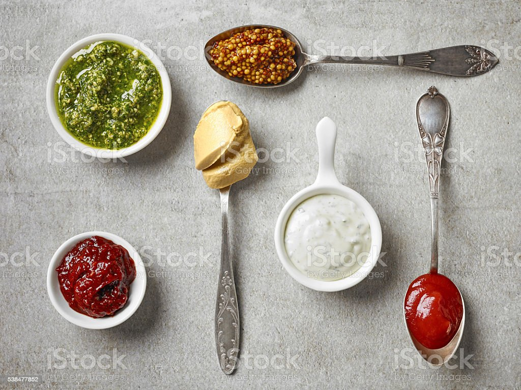 various sauces in bowls and spoons stock photo