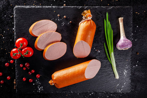Various sausages and smoked products lie on a black board, sausage, sausages, ribs, rolls. Top view, overhead. Flat lay