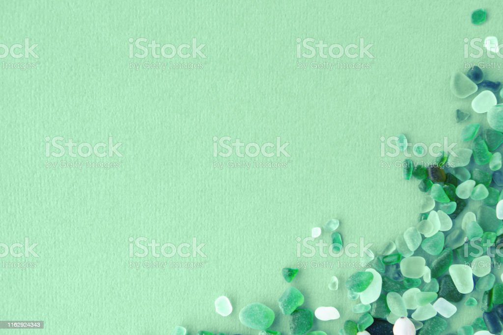 Close up of various sea glass pieces on trendy neo mint background....