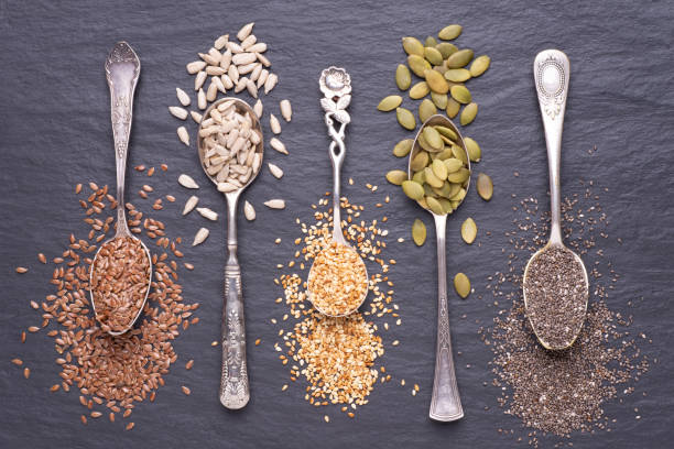 Various seeds in spoons on a black stone background, top view stock photo