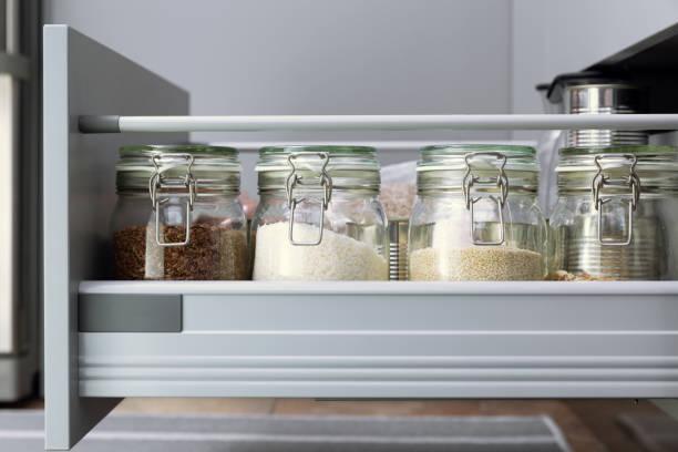 verschiedene samen in lagergefäßen in holle, weiße moderne küche im hintergrund. intelligente küchenorganisation - küchenorganisation stock-fotos und bilder