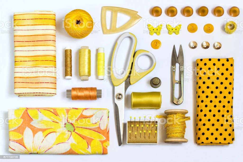 Various sewing accessories and tools yellow shades stock photo