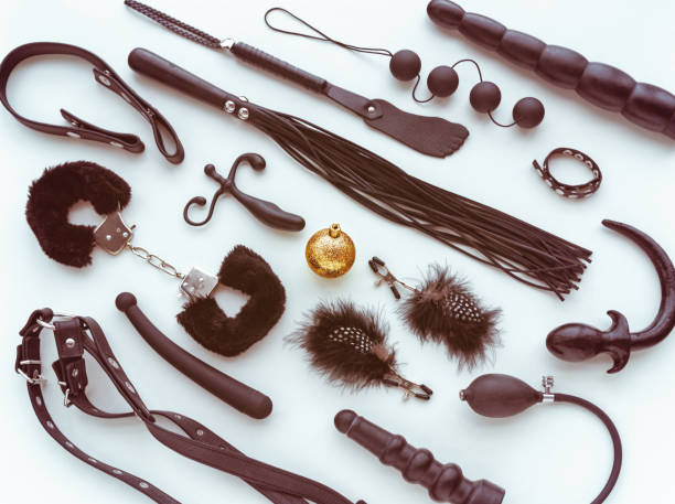 Various sex toys (whip, dildo, handcuffs, butt plug, anal balls and other) and a golden christmas ball. View from above. Image for the festive season and sales. New Year or Christmas background sex toy stock pictures, royalty-free photos & images