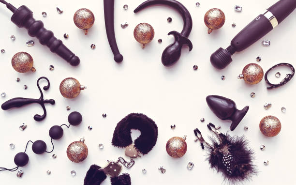 Various sex toys (dildo, anal balls, vibrator, fur handcuffs and others), golden christmas balls and crystals are arranged in a circle. New Year or Christmas festive background for Sex shop sex toy stock pictures, royalty-free photos & images
