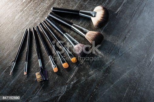 847152928 istock photo various shape cosmetic brush set on black stone 847152590