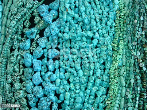 Many strands of turquoise beads for sale at a market.