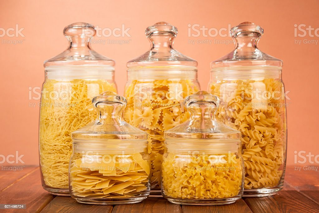 Various shapes of pasta in jars on terracotta background. photo libre de droits
