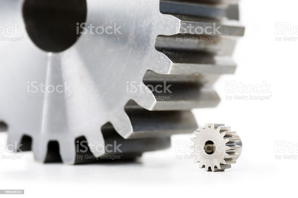 Various size gears, larger gear intimidates smaller one stock photo