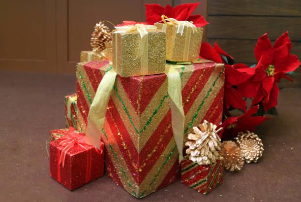 verschiedene größe von geschenk-boxen stapel mit trockenen kiefernzapfen und weihnachtsstern kunstblumen für weihnachtsschmuck - glitter farbige wände stock-fotos und bilder
