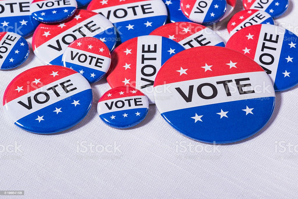 Various size Patriotic VOTE buttons on white table cloth stock photo