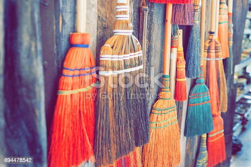 istock various sizes of brooms are hanging and looking untidy on the wooden wall ,process vintage style with soft focus . can be used for background or wallpaper . 694478542
