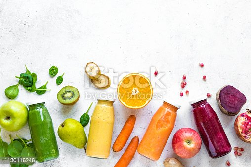 Various smoothies or juices in bottles and ingredients on white, healthy diet detox vegan clean food concept, top view, copy space.