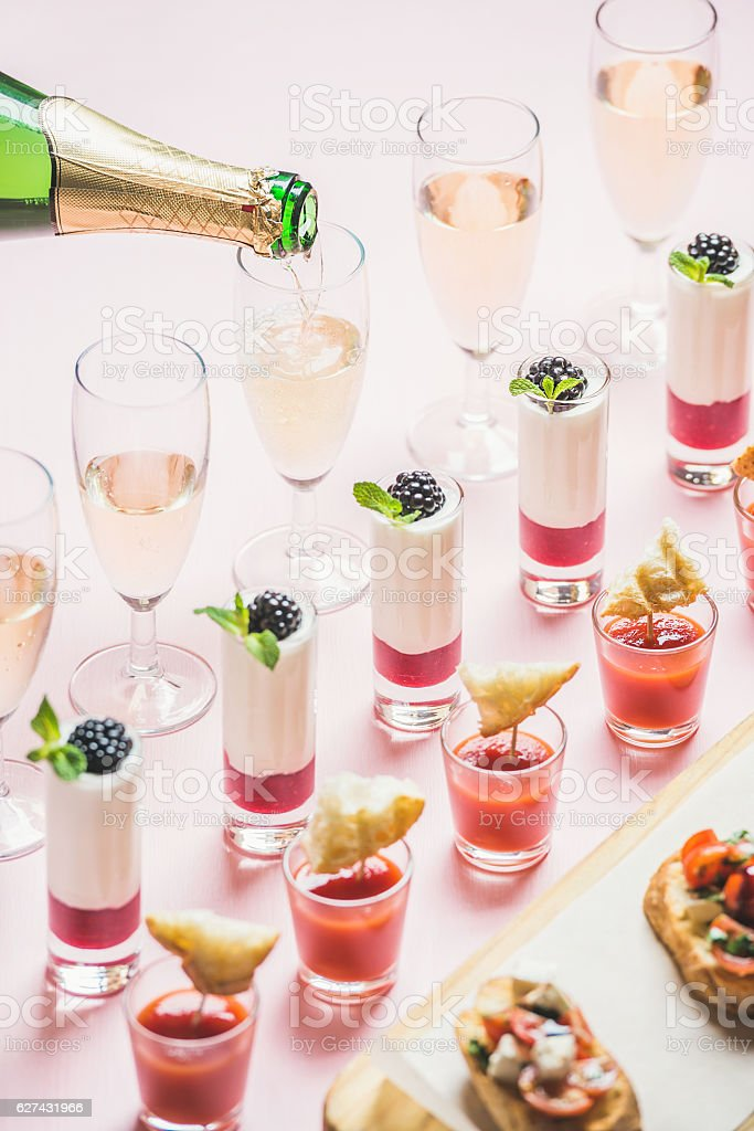 Various snacks, brushettas, gazpacho shots, desserts, champagne pouring to glasses stock photo