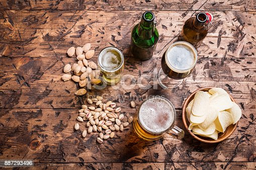 Beer style- bottle, various sort of beer in the glass and nuts on wooden table. Free space for text. Top view