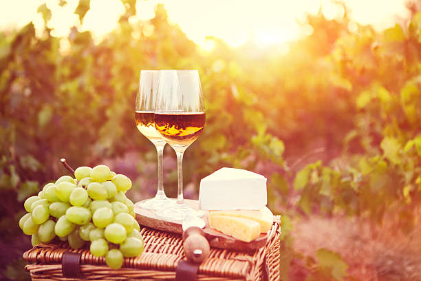 various sorts of cheese and two white wine glasses - französische land tisch stock-fotos und bilder